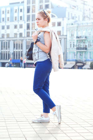 tied in: Young adult caucasian woman with blond hair tied in a bun in glasses wearing blue pants, tee-shirt and cardigan street fashion look