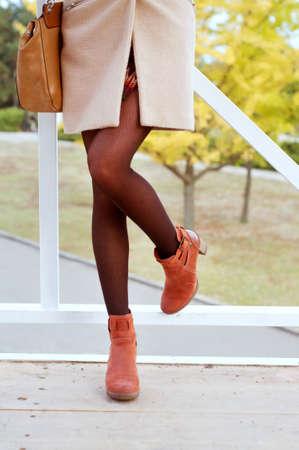 mini falda: La mujer llevaba medias negras y botas de gamuza de color naranja vestido con abrigo beige y mini falda. Moda de otoño;
