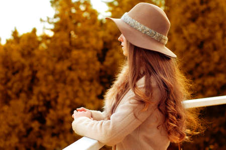 fedora: Woman with long red hair, fedora hat and fur coat standing on the balcony in the woods in autumn. Melancholic mood.