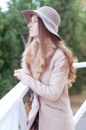 ojos verdes: Elegant caucasian redhead woman with freckles and green eyes in fedora hat and beige coat with fur. City street fashion.
