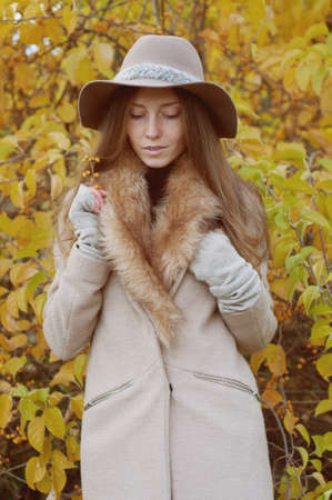 Retro look. Beautiful ash blond with freckles, long hair in fur collar coat and fedora hat outdoors in autumn
