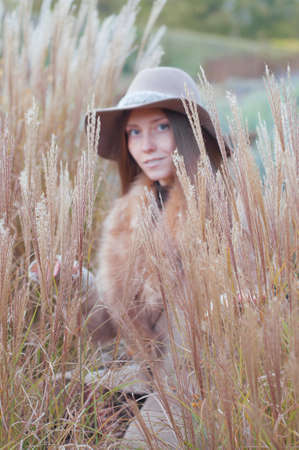 fedora: Woman in beige fur coat and felt fedora hat in the dry autumn field, selective focus. Stock Photo