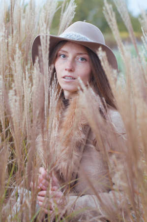 fedora: Woman in beige fur coat and felt fedora hat in high grass dry autumn field