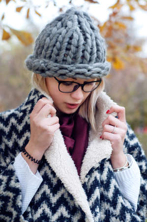cardigan: Student girl in autumn park wearing glasses, warm cardigan and thick knitted hat. Fall street style city look.