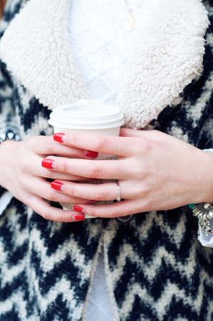 cardigan: Woman in warm knitted black and white cardigan holding cup of coffee in paper cup. Beautiful manicure red gel nails.