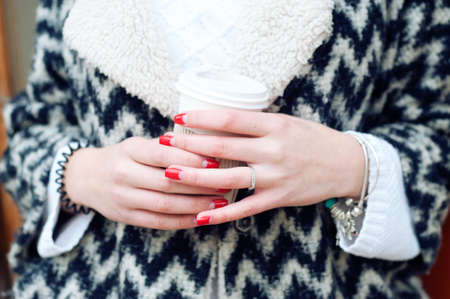 red cardigan: Woman in warm knitted black and white cardigan holding cup of coffee in paper cup. Beautiful manicure red gel nails.