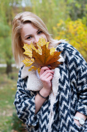 cardigan: Cute smiling blond woman in black and white knitted warm cardigan strolling in autumn park