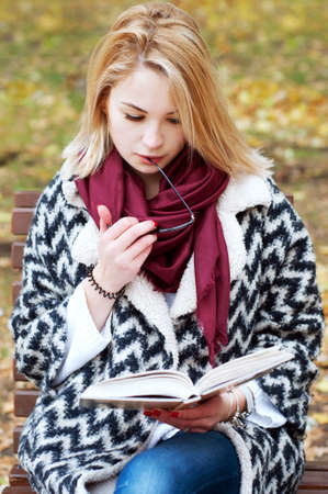 Cute smiling blond woman in black and white knitted warm cardigan reading in autumn park