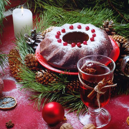 sugar powder: Christmas table setting. Bundt cake pudding sprinkled with sugar powder decorated with and mulled wine.