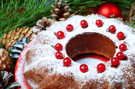 sugar powder: Christmas table setting. Bundt cake pudding sprinkled with sugar powder decorated with red currant.