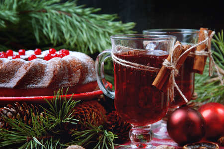 Christmas table setting. Bundt cake pudding sprinkled with sugar powder decorated with red currant and mulled wine.