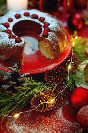 sugar powder: Christmas table setting. Bundt cake pudding sprinkled with sugar powder decorated with red currant and mulled wine.