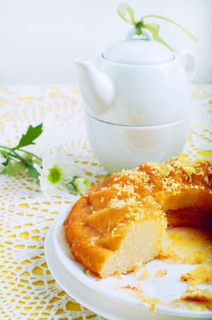 Yellow summer table setting with lemon bundt cake, white plates, teapot and chrysanthemum flowers in a glass vase