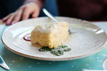 A piece of napoleon cake dessert made of thin layers of pastry with custard filling sprinkled with sugar powder, mint leaves on a plate