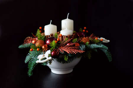 Winter table centerpiece wreath with candles, new year toys, spice and fir branches Stock Photo