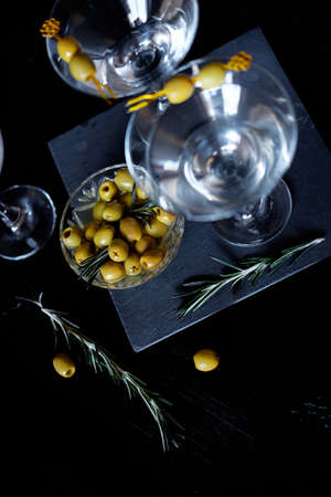 margarita cocktail: Margarita cocktail alcohol drink in glass with green olives on black backdrop Foto de archivo