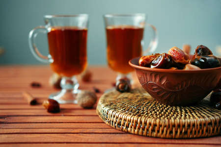 Bowl of dried dates and other spices on old wooden table with tea in glasses. Stock Photo
