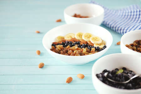 Healthy breakfast. Oatmeal in a white bowl with banana, almond nuts, blueberries and raisins.