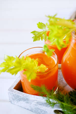 Fresh carrot juice poured into glasses, green celery, dill weed. Healthy vegetarian food concept.