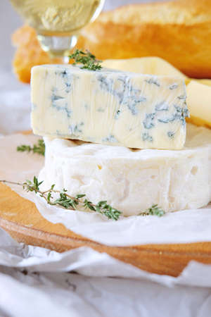 Cheese plate with different kinds of cheese with a glass of white wine and baguette Stock Photo