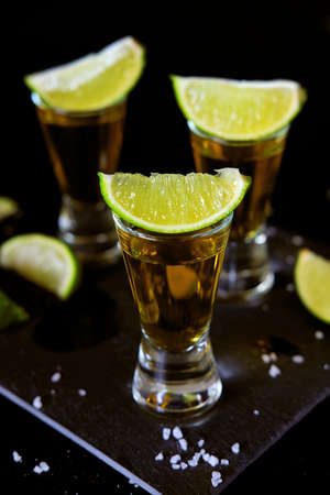 Strong alcohol drinks. Tequila glass shots in the bar with salt and lime slices.