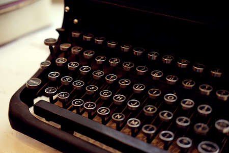 qwerty: Old fashioned iron typewriter console closeup in black. Retro objects. Stock Photo