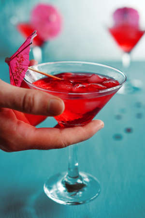 toothpick: Raspberry cocktail with ice and paper umbrellas. Summer refreshing alcohol drinks for parties.