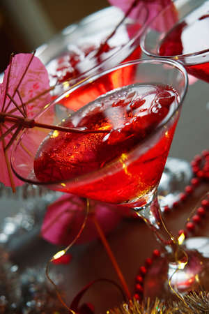 Raspberry cocktail with ice and paper umbrellas. New year refreshing alcohol drinks for parties.