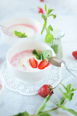 Cold creamy strawberry soup sprinkled with coconut chips with a scoop of ice cream and mint leaves. Cold summer dessert.