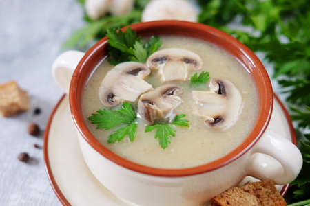 Fresh mashed mushroom soup decorated with green parsley, bread croutons and pepper on grey background