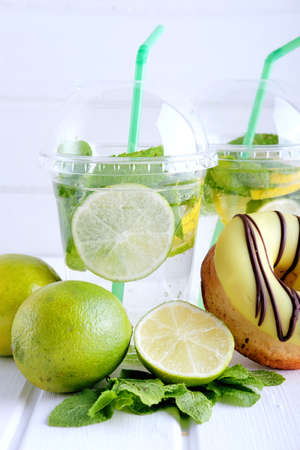 Refreshing summer drink. Lime and mint mohito in plastic cocktail glasses with green straws and sweet doughnut with green icing. Stock Photo