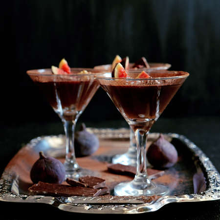 Chocolate mousse dessert with cinnamon, walnuts and figs served in cocktail glass Stock Photo