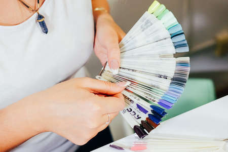 Gel nail colour array palette at beauty parlour. Beautician choosing nail colour.