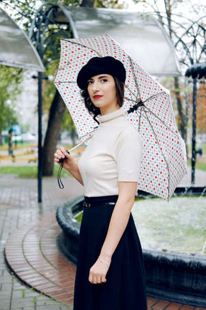 Young Parisian woman wearing black beret walking under the rain with dots umbrella. melancholic autumn mood.
