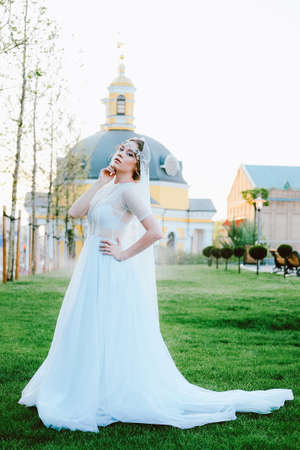 Charming young bride in white dress and veil walking to the church in the summer evening
