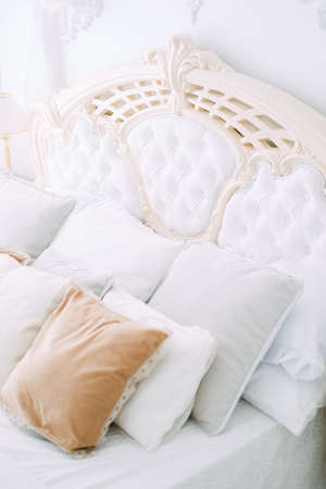 Luxury bedroom interior design in white and beige colors with tulle baldachin over the bed, plasterwork detail on the walls Stock Photo