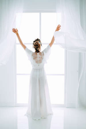 Tender elegant young brunette bride with hairdo, hairpin and bridal makeup wearing white peignoir standing back near the window waiting. Bridal boudoir. Stock Photo