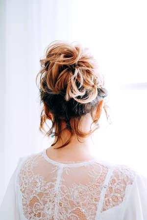 Tender elegant young brunette bride with hairdo, hairpin and bridal makeup wearing white peignoir. Bridal boudoir.