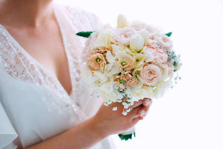 Bridal morning. Beautiful bride getting ready for the wedding ceremony and holding the bouquet.
