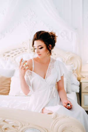 Sensual brunette in silk white robe waiting on the bed looking calm and relaxed and spraying on her perfume