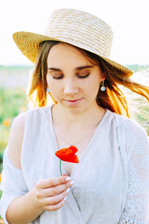 Happy young blond woman smiling in the field of poppies wearing linen jumpsuit, hat and woven basket with wind blown hair Stock Photo