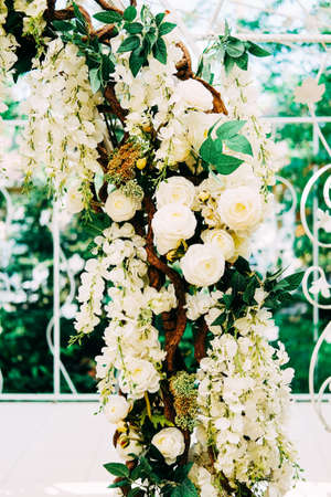 Getting ready for the wedding ceremony. Wedding arch decorated with white flowers