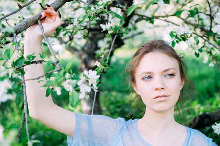 Calm and pretty young woman in the garden wearing transparent blue dress 写真素材