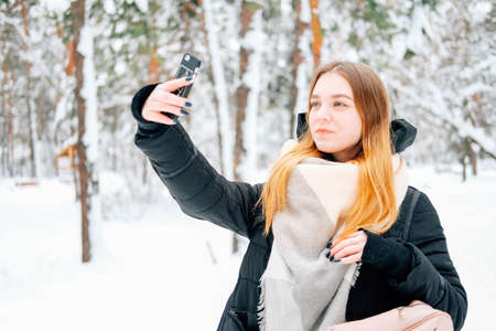 Attractive blond young adult woman walking through winter forest full of snow wearing casual outfit of black parka, jeans, pink leather boots and backpack and beige shawl and texting to friends