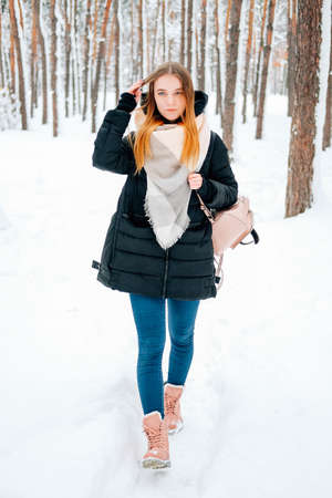 Attractive blond young adult woman walking through winter forest full of snow wearing casual outfit of black parka, jeans, pink leather boots and backpack and beige shawl