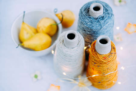Three natural gray, yellow and white tweed yarn in bobbins for knitting and handmade in winter