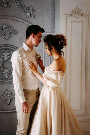 Zwei junge Liebende bereiten sich auf die Hochzeit vor. Braut, die den Knopflochblumenstrauß anzieht.