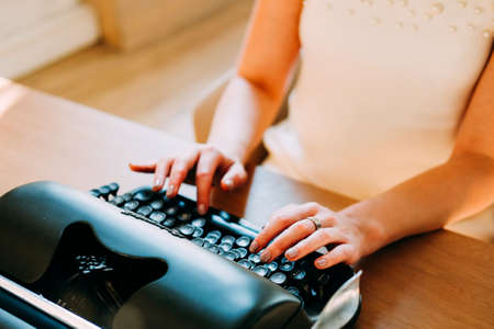 Professional occupation. Secretary in white dress and long black straight hair typing documents on the typewriter machine Banco de Imagens