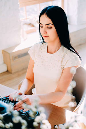 Professional occupation. Secretary in white dress and long black straight hair typing documents on the typewriter machine