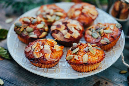 Healthy fall vegetarian dessert. Apple cupcake with pumpkin, almond seeds and spices.